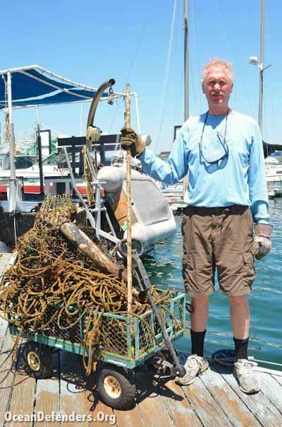 Jim Lieber stands next to some of the marine debris pulled from an area just outside of the LA Harbor Lighthouse.