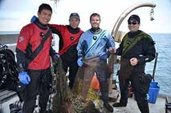 Andy The, Steve Millington Eric Humphreys, and Shingo Ishida with hauled-up net on rear deck of the <em>Clearwater</em>