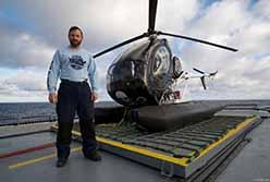 Volunteer Chris Aultman with helicopter in ODA shirt