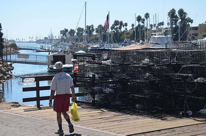 Pile of lobster traps ready to load onto boat with pedestrian
