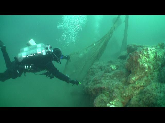 ODA Divers carefully cut abandoned squid net away in order to lift it to the surface and haul it away.