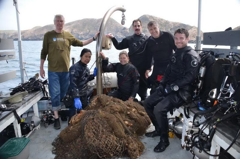 ODA Volunteer Dive Crew proudly display the abandoned squid net they removed, making the ocean more safe for wildlife!