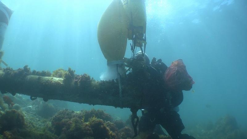 ODA Volunteer Diver Kim Cardena attaching lift bag to sunken wreck's mast