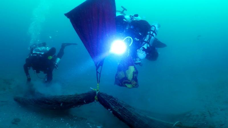 ODA volunteer SCUBA divers Jeff Larsen and Kim Cardenas ridding ocean of abandonded squid net.