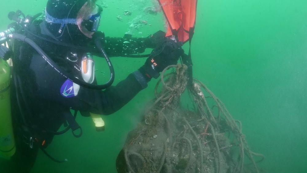 Scuba diver attaches float bag to abandoned fishing gear