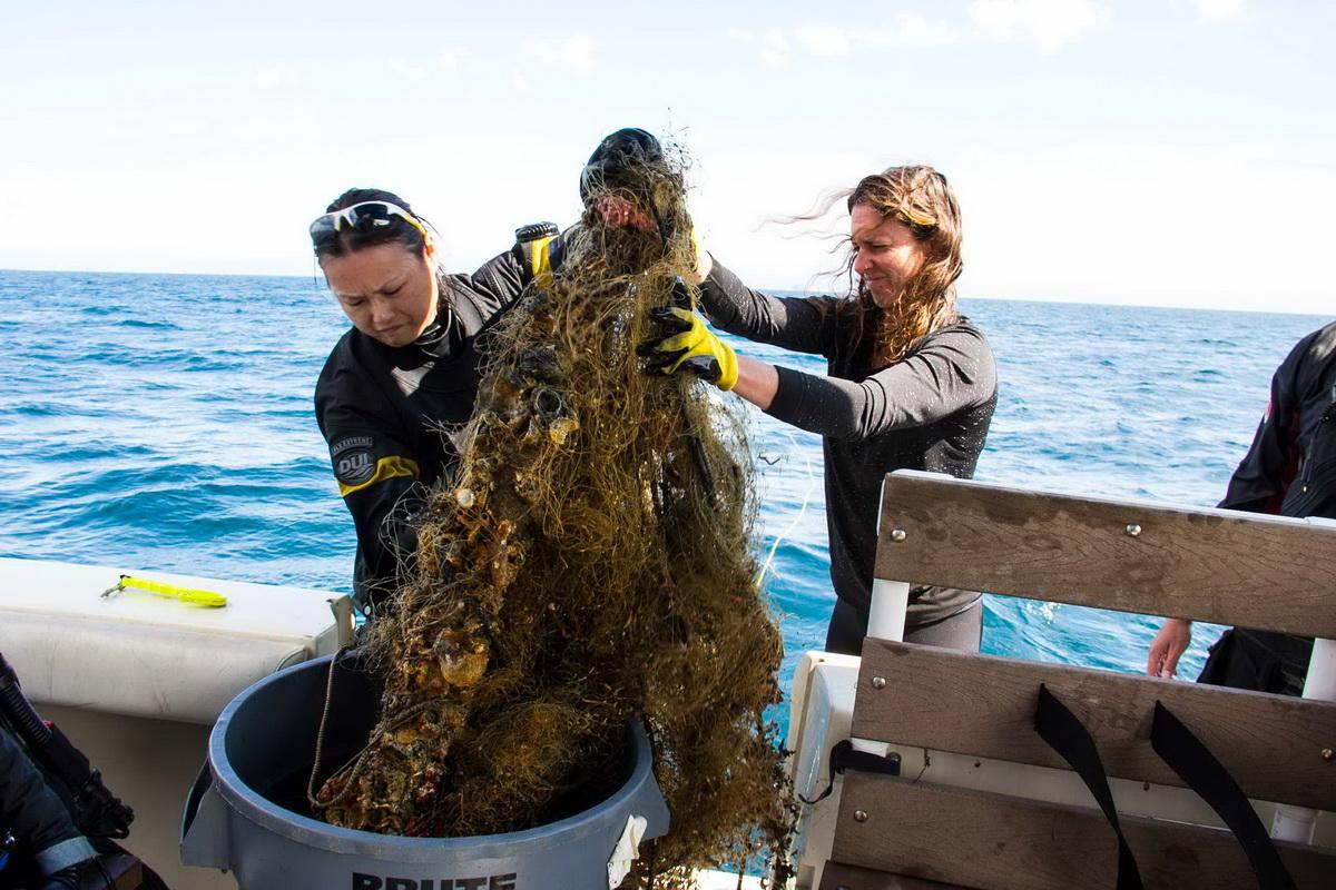Female crew removes abandoned fishing net from ocean